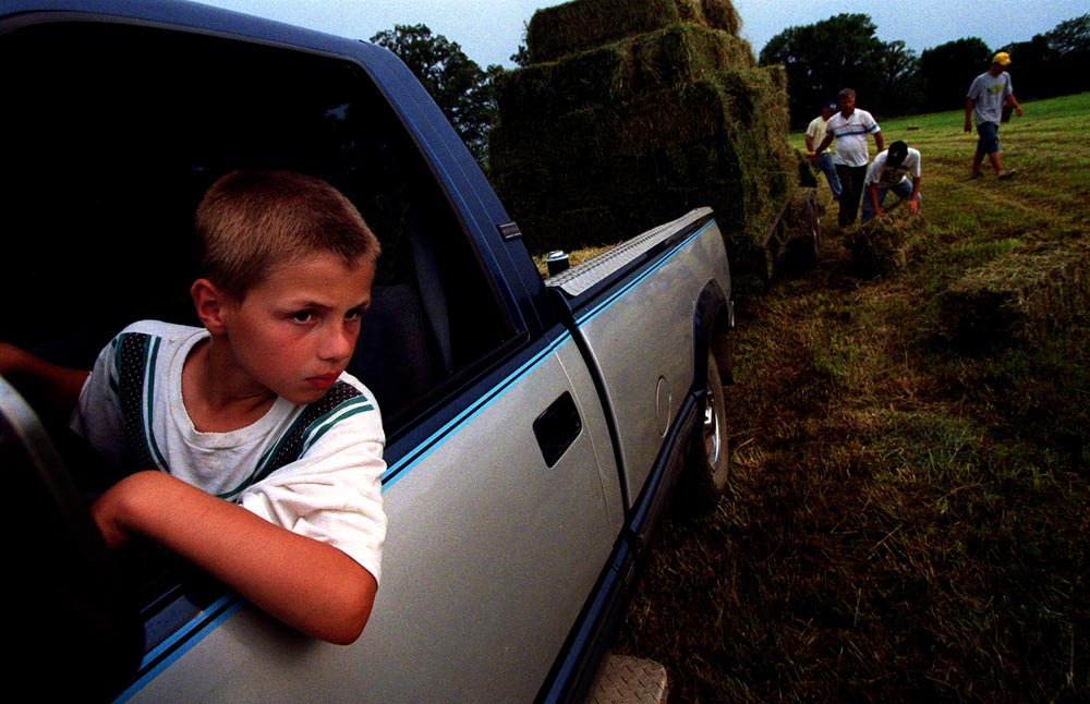 Greg Fick receives plenty of help from his family and the community when his hay needs bailing. His son John, 8, normally drives the truck because he is too small to lift the bales.