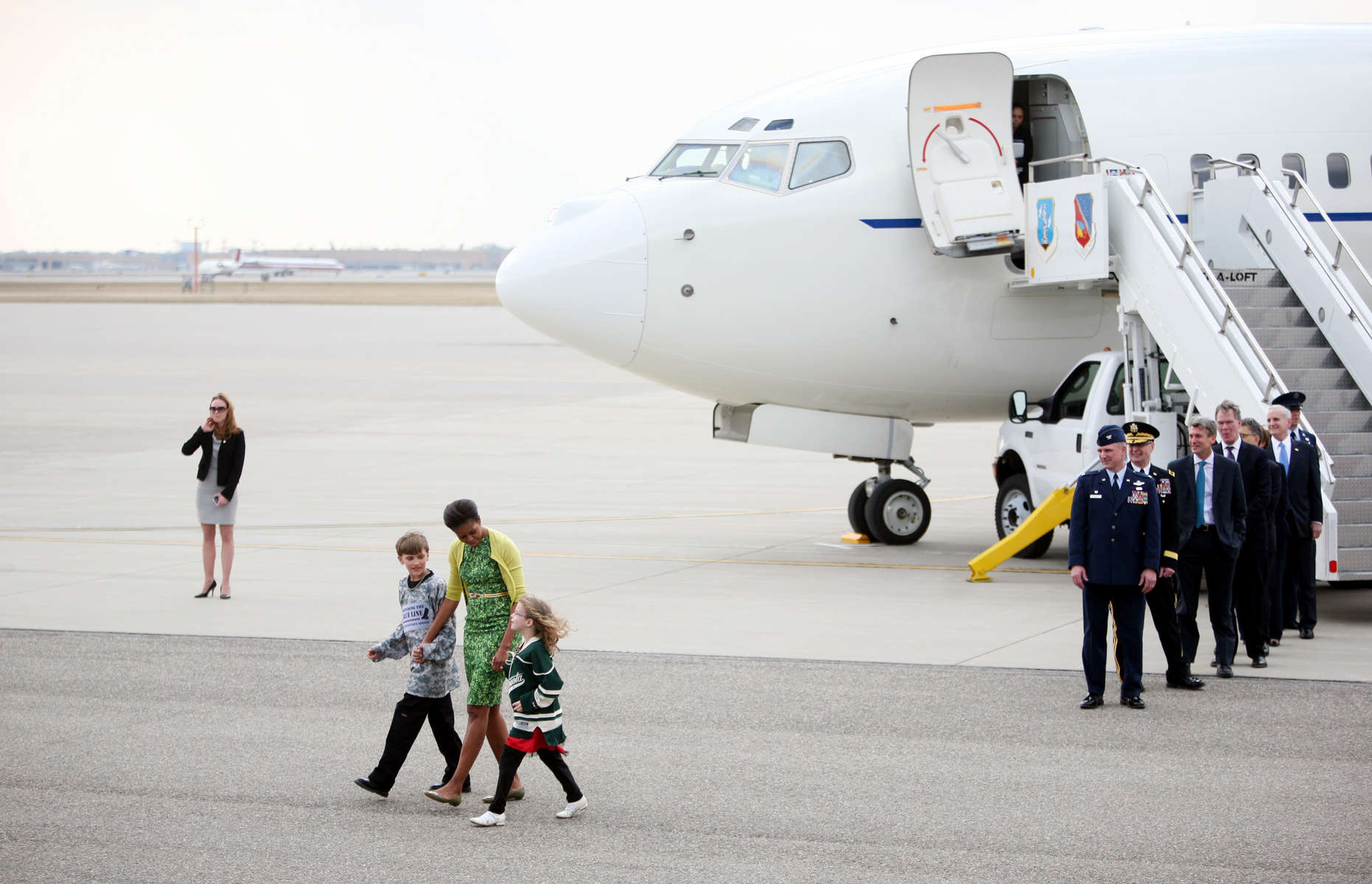 Joseph Hudella, 10, and Megan Soukup, 9, escort First Lady Michelle Obama to meet with Minnesota National Guard members and their families at Minnesota Air National Guard Base's 133rd Airlift Wing in St. Paul, Minn.