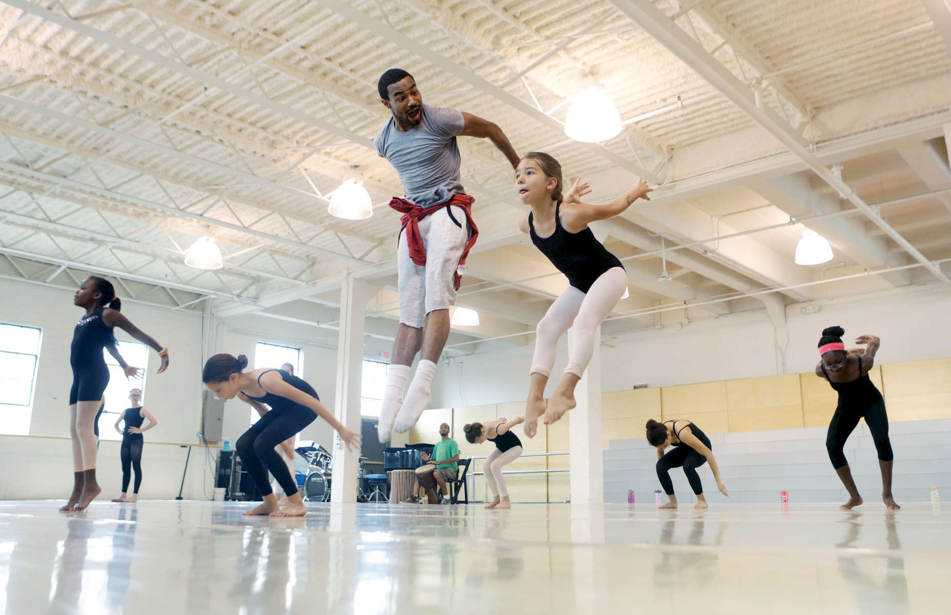Teacher Darwin Black and student Lydia Salazar, 8, warm up during a modern dance class at TU Dance in St. Paul, Minn. The dance company, which offers classes and workshops, recently moved to a new facility along University Avenue in St. Paul.