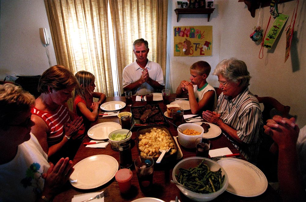 Greg Fick leads a prayer before sharing a meal with his family in the same dining room he ate in as a child. Greg and his wife, Bert, raise six children on their cattle farm, and despite hectic schedules demanding workloads, the family normally gathers together at mealtime.
