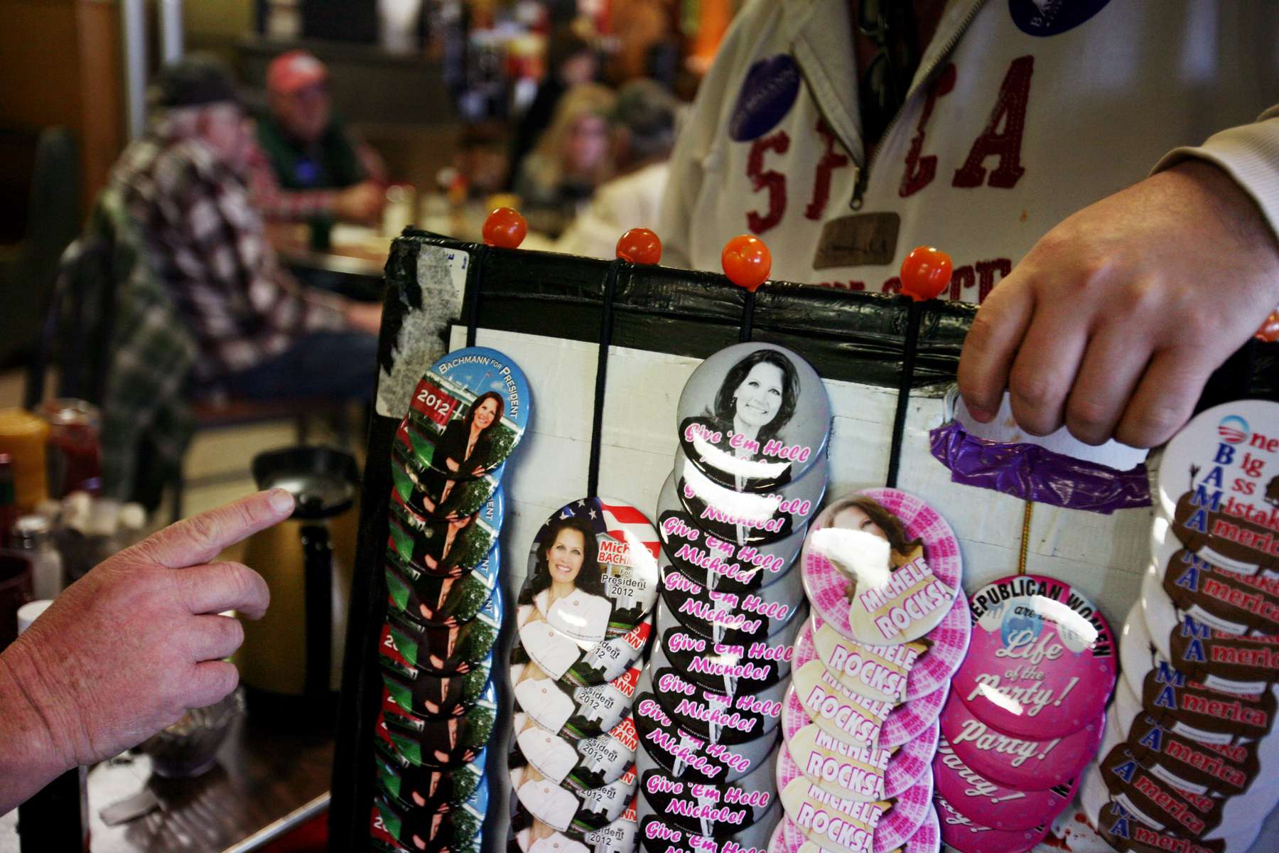 A Michele Bachmann supporter selects a button from a vendor during Bachmann\'s bus tour stop at Family Table Restaurant in Osceola, Iowa.