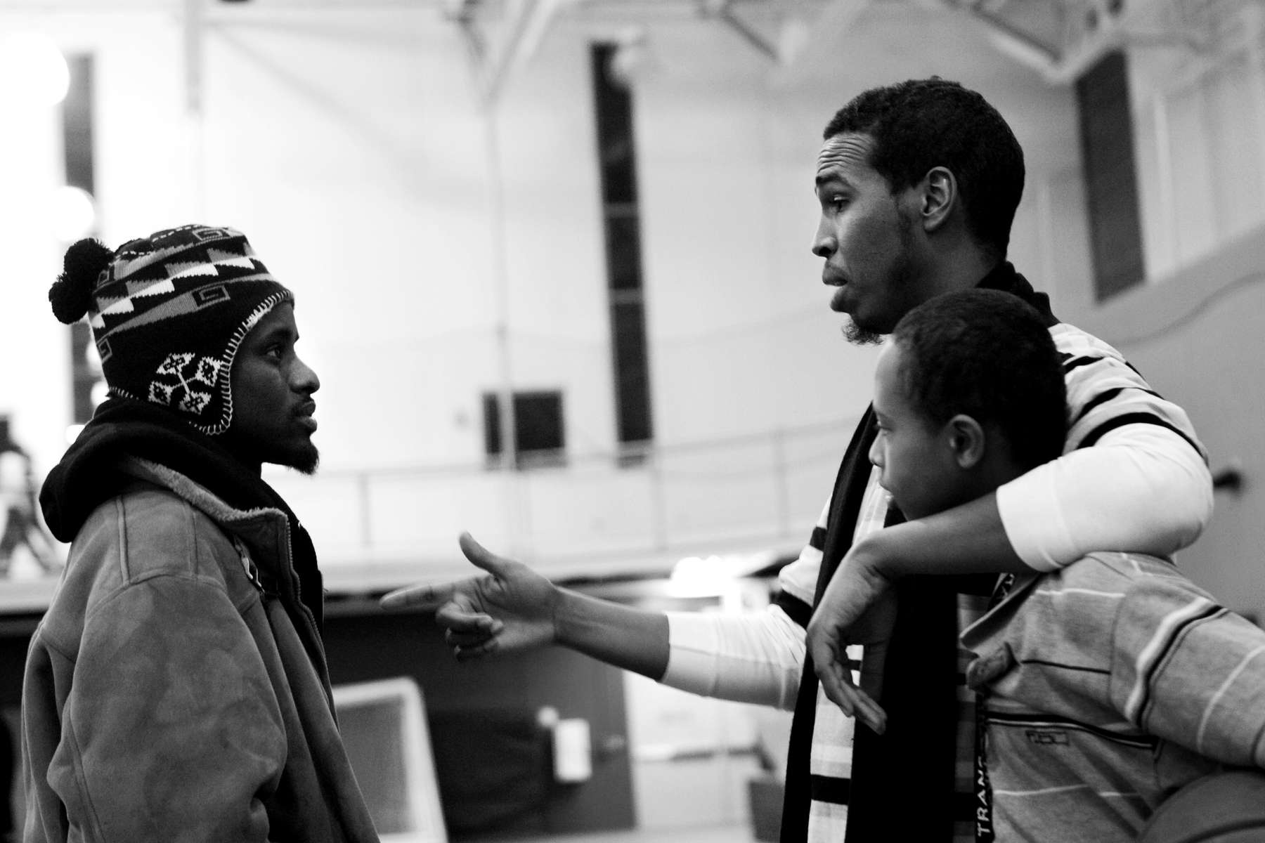 Abdulahi Farah, right, talks with young men during a basketball tournament at the Midtown Y.W.C.A. in Minneapolis. Farah, who established the Somali Youth Network Council, says basketball helps keeps at-risk youth off the streets.