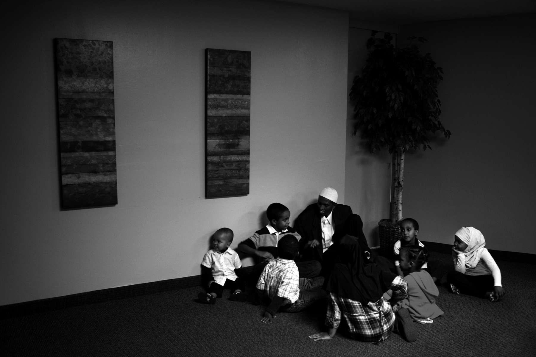 Liban Karshe, middle against wall, shared stories with a group of children before Iftar in Edina. Iftar is the evening meal when Muslims break their fast during the month of Ramadan.