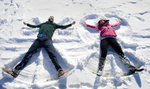 engaged couple making snow angels during their snowy Hoboken engagement session. Hoboken wedding photographers