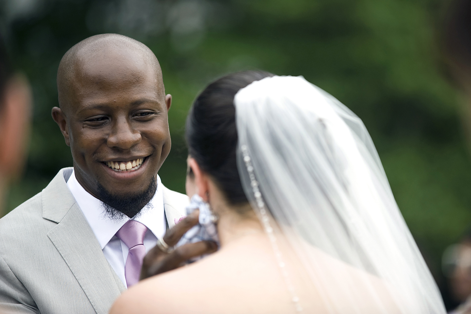 groom wipes away tear as bride cries during wedding ceremony at The Water Witch Club at Monmouth Hills. Jersey Shore wedding photographers