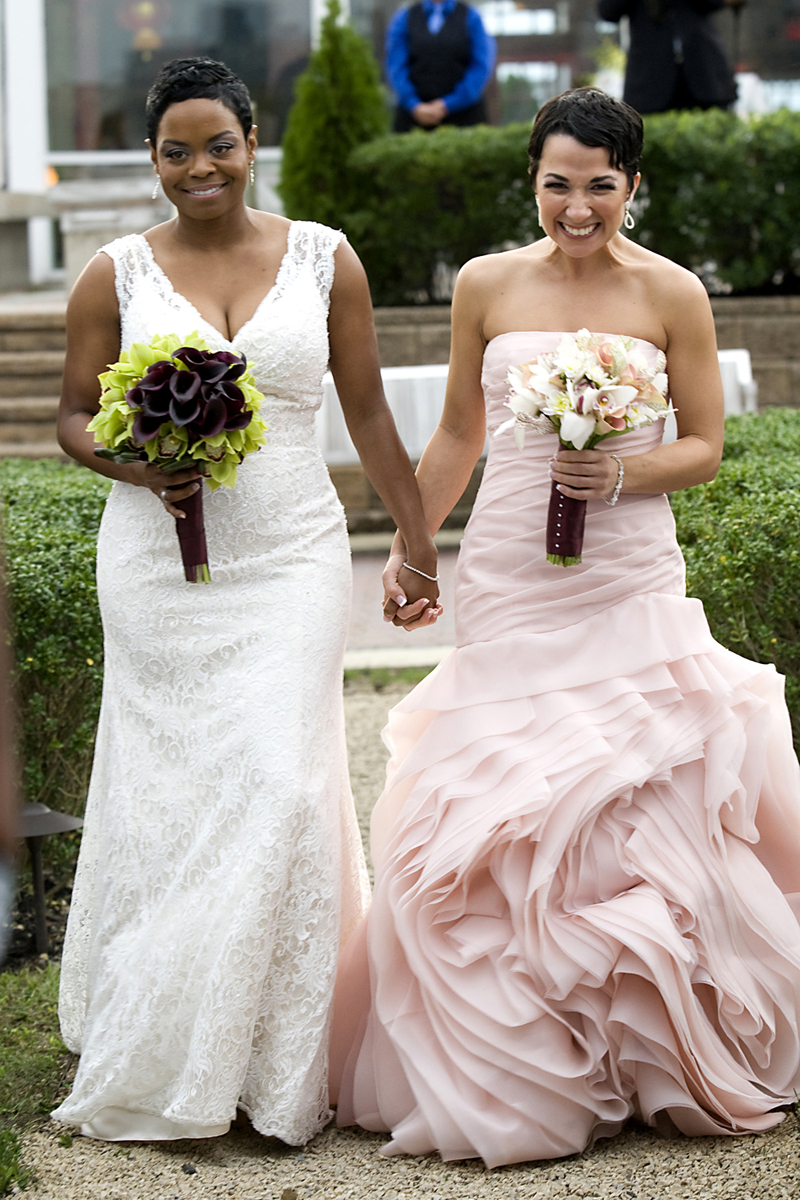 Brides walk down the aisle at the start of their wedding ceremony at Liberty House. NYC gay-friendly wedding photographers