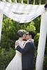 bride and groom kissing at conclusion of wedding ceremony at Queens Botanical Gardens. NYC wedding photographers