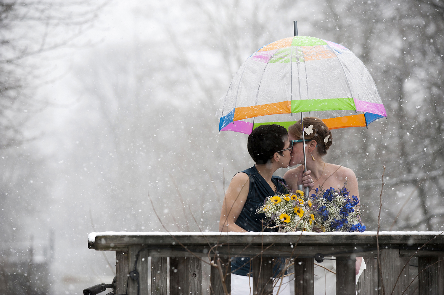 Brides kissing in the snow under colorful umbrella during their winter wedding at Lambertville House. NJ wedding photos