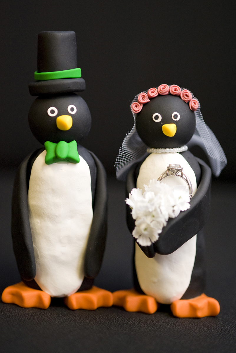 Creative ring shot of penguin cake toppers with wedding rings at Mystic Aquarium by Destination Wedding Photographer. Hoboken Wedding Photographers