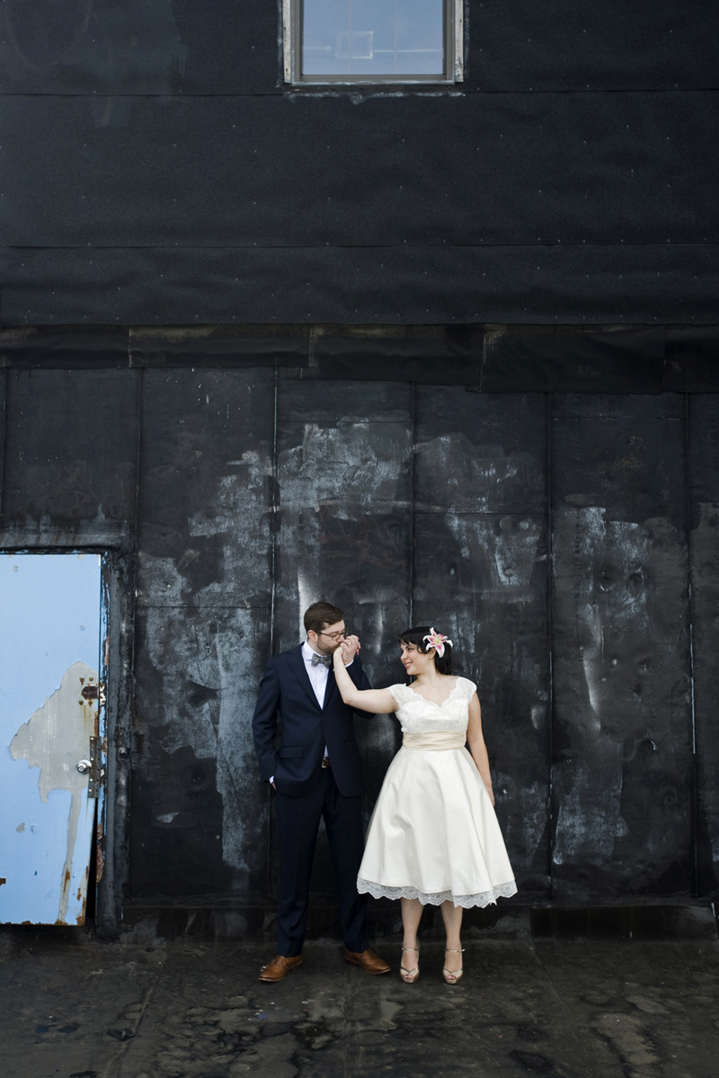 Portrait of bride and groom on roof of reBar in Brookln kissing against blue door.