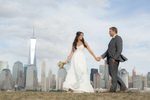 Bride and groom walking against the NYC skline at Liberty State Park in Jersey City.
