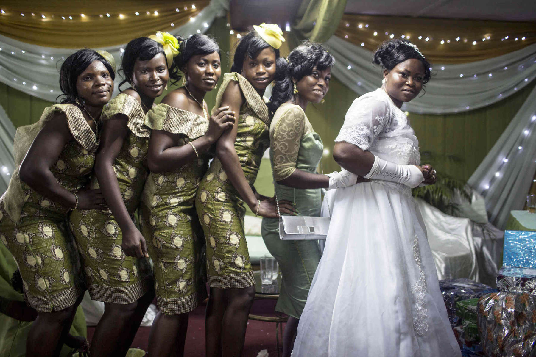 Bride Temitope Caulker poses with her bridesmaids, who in typical Nigerian fashion, wear outfits that match the decor of the wedding hall.