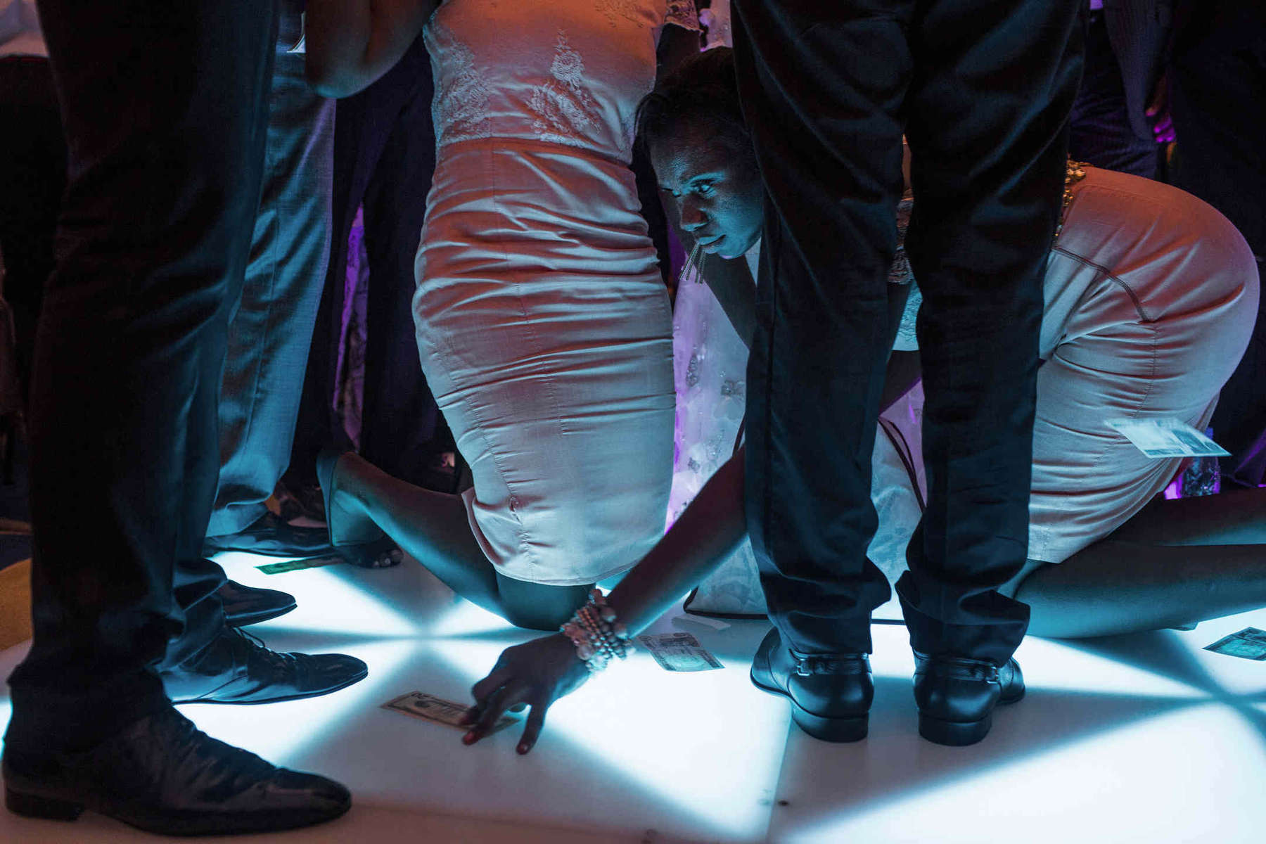 A bridesmaid collects {quote}spray{quote} -  Naira notes (and sometimes dollars too) thrown at the couple as they dance. While spraying is technically illegal and considered an abuse of currency by the Nigerian government, the practice is common and shows the importance of displaying wealth and excess during celebrations.