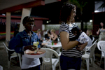 A woman who works in conservation holds a baby chimpanzee at a Lebanese restaurant frequented by expatriates in Monrovia as a waitress brings here a margarita. October, 2011.