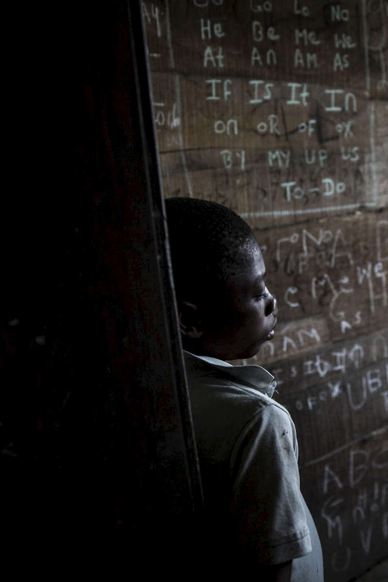 A young boy at the former Tubman palace in Harper. Most of the children who live there don't have money to go to school. While education is supposed to be free, uniforms, books, and transportation money is often out of reach for many, especially squatters at a rainy abandoned mansion. Some kids do a bit of learning on their own.  Photo by @glennagordon for @smithsonianmag#Liberia #Africa #WestAfrica #EverydayAfrica #antebellum #architecture #Harper #remote #seaside #decay #mansion #Tumbans