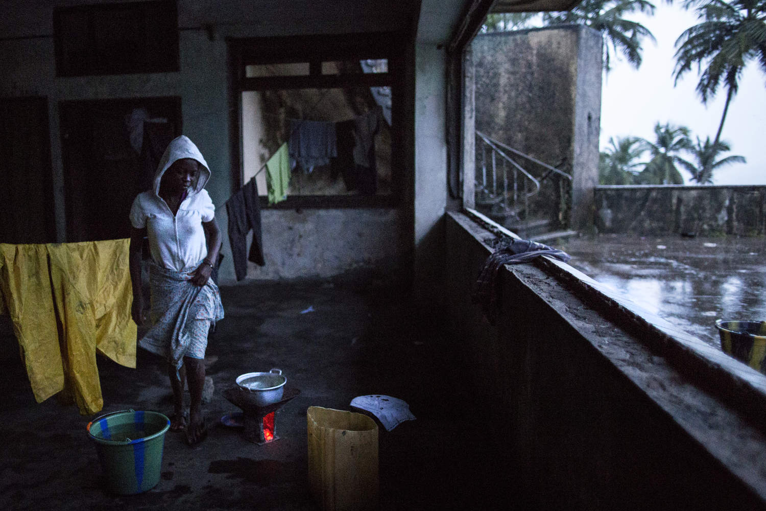 Patience Wallace, 14, heats water for a bath on a cold and rainy day. Former President Tubman's house in Harper, once referred to as the Tubman Palace, is now derelict and filled with squatters.  Photo by @glennagordon for @smithsonianmag#Liberia #Africa #WestAfrica #EverydayAfrica #antebellum #architecture #Harper #remote #seaside #decay #mansion #Tumbans