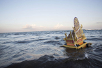 A golden {quote}adegan{quote} throne the carries the cremated remains of a person floats out to sea at the end of a long funeral procession in Bali, Indonesia. The god of the sea is now responsible for the soul of the deceased.