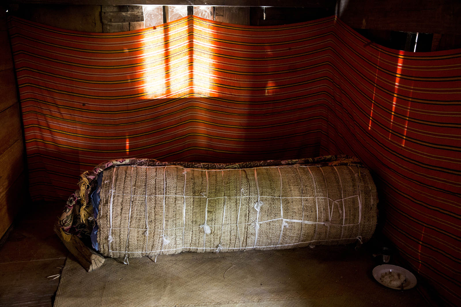 A traditionally wrapped corpse in the barn of a home in Toraja, a remote part of Indonesia where the deceased are kept in the house for years as the family saves up money for the elaborate funeral procession. They also take their time to say goodbye, and the pain of processing death can be much more gradual.