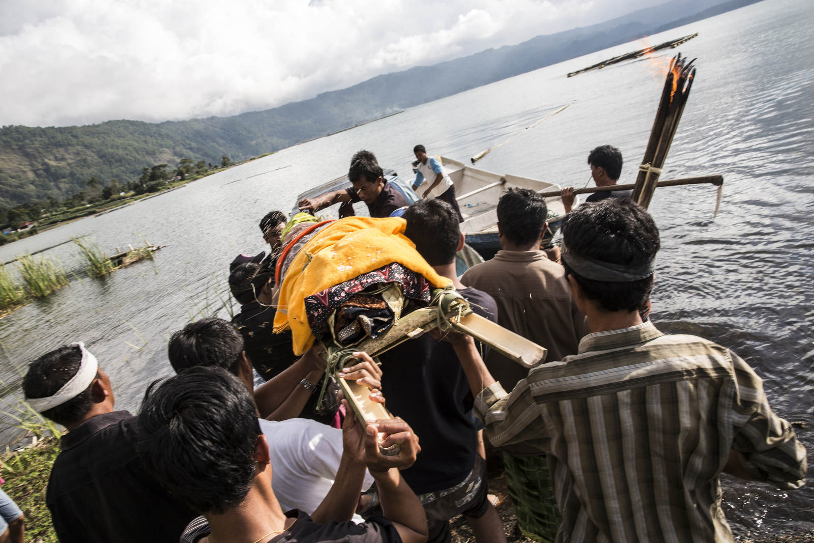 Wayan Sudira's body is carried on to a boat to take to spot on the shores of Lake Batur in northern Bali.