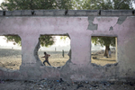 A young boy runs pas the remains of Gamboru Primary School, which was bombed by Boko Haram in 2014.