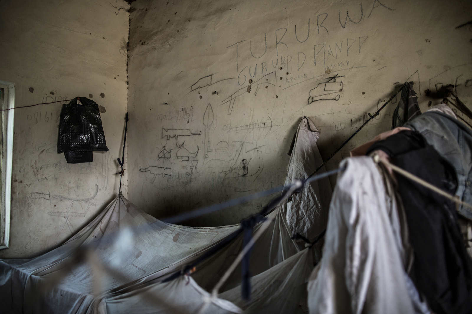 Drawings of guns and helicopters are on the wall of the men's room at an Internally Displaced Persons camp called Teacher's Camp on the outskirts of Maiduguri. Men and women sleep separately, everyone in incredibly cramped corners. The camps in Maiduguri are often in abandoned public works projects.