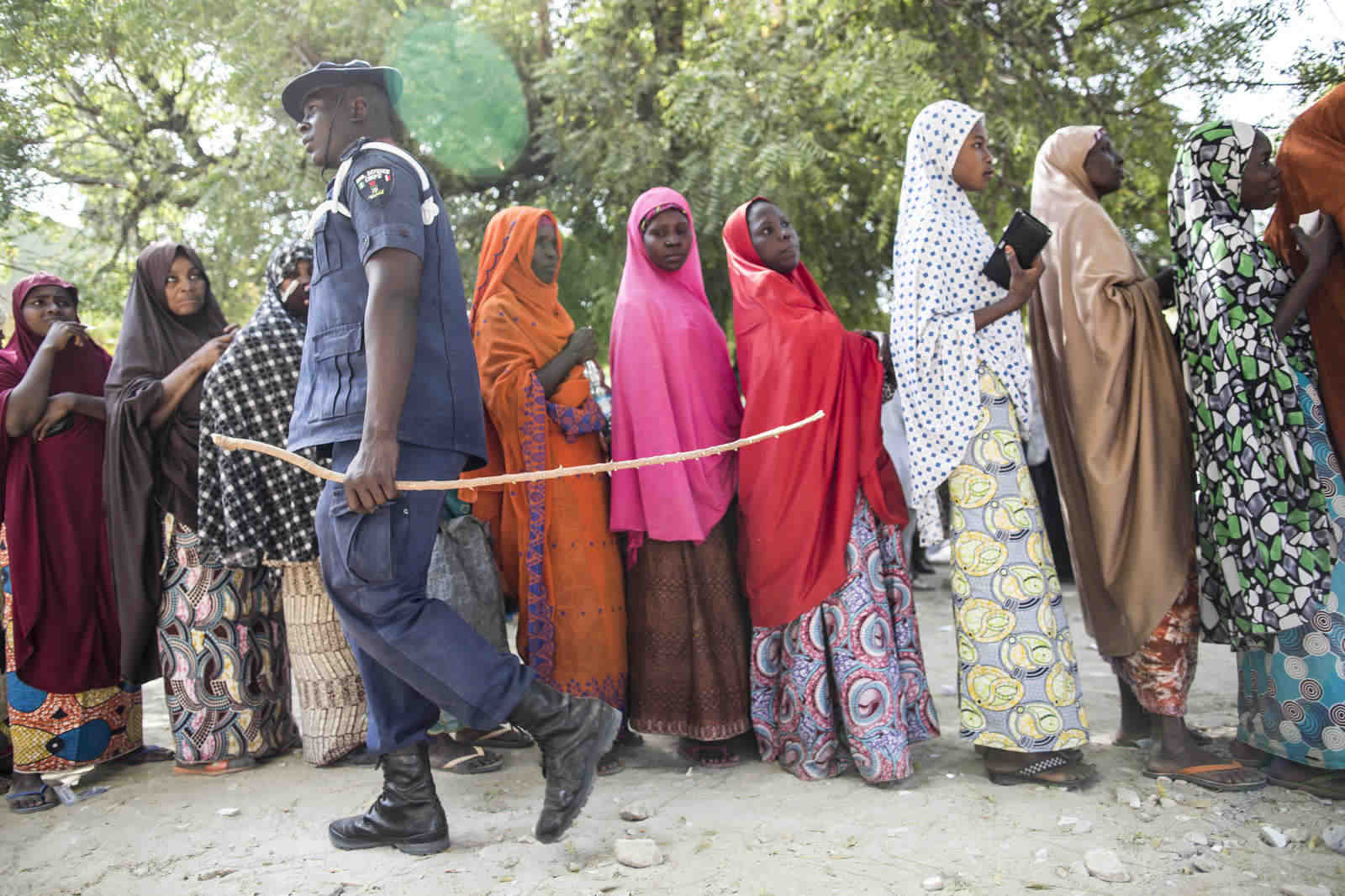 A security officer monitors women who are waiting for a food distribution by African Health Implementation and Facilitation Foundation, a local NGO.