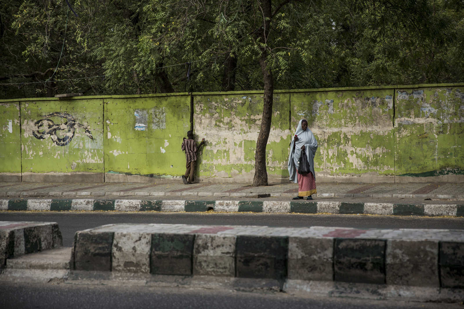 A young boy looks through a crack in the wall outside of the Maiduguri Zoo. Once a tourist attraction, during the height of Boko Haram's power, members would roam the zoo and use it as a place to smoke marijana and do other things considered haram, or morally wrong.