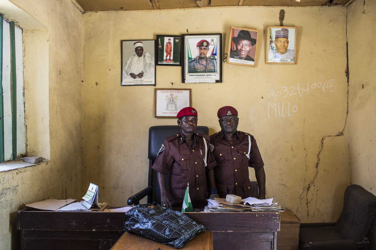 Mohammed Abas Kgava, the spokes person for the vigilantes, poses for a portrait with State Commander Adamsi Mohammed Tar in the office of the State Vigilantes. They are ready to use their local knowledge of the bush and the forrest to go and look for the girls. They are armed only with bows and arrows and hunting rifles, while Boko Haram is often said to be better armed than the Nigerian army.