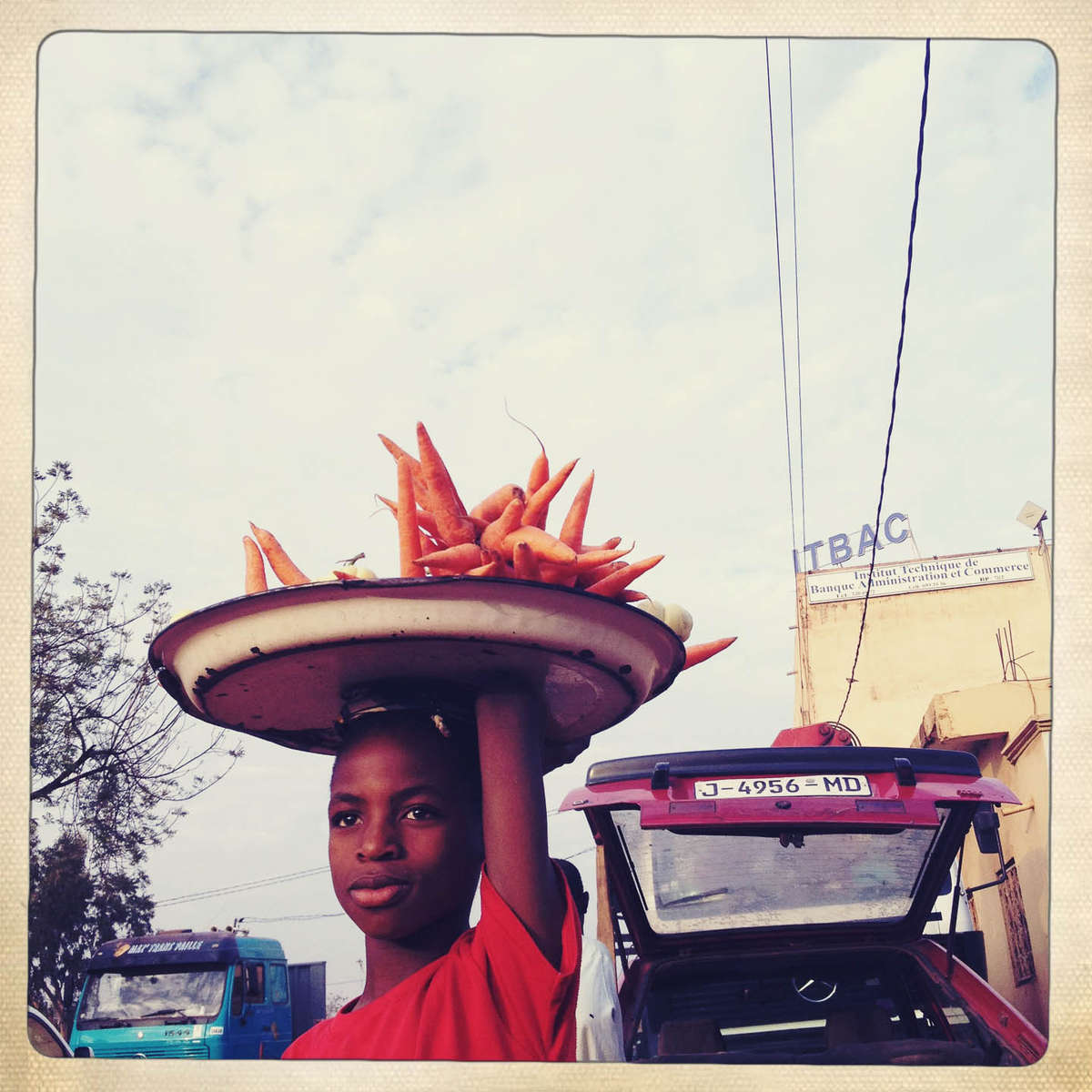 A boy sells carrots at a bus station in Bamako, Mali. January 2013.