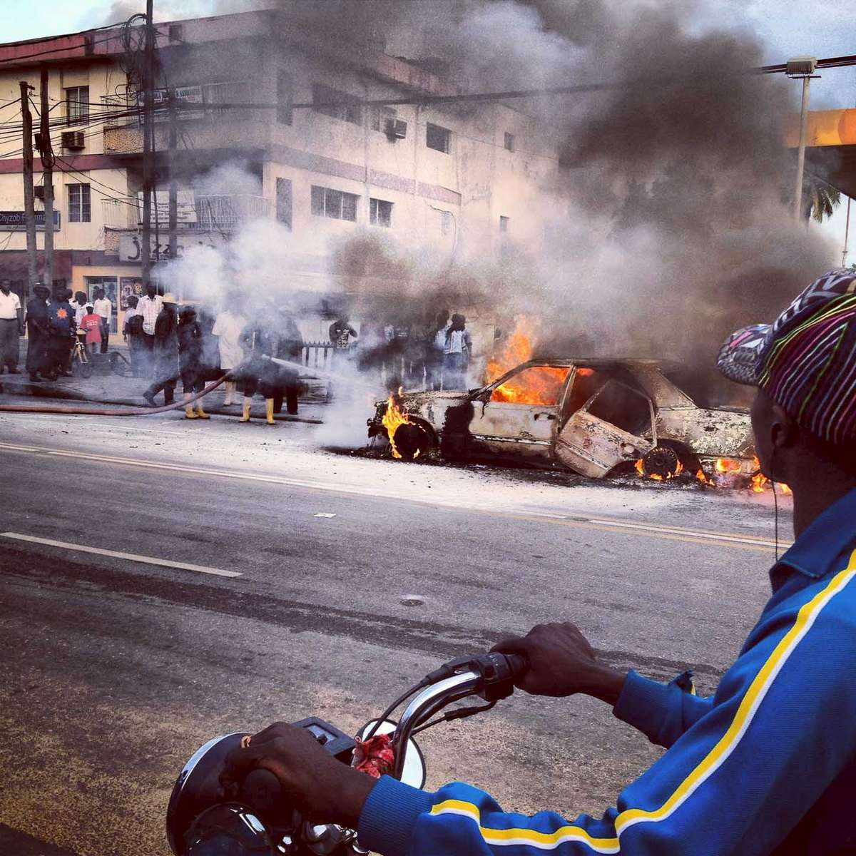 A motorbiker stops to watch a car that caught on fire on Awolowo Road in Lagos, Nigeria. October 2012.