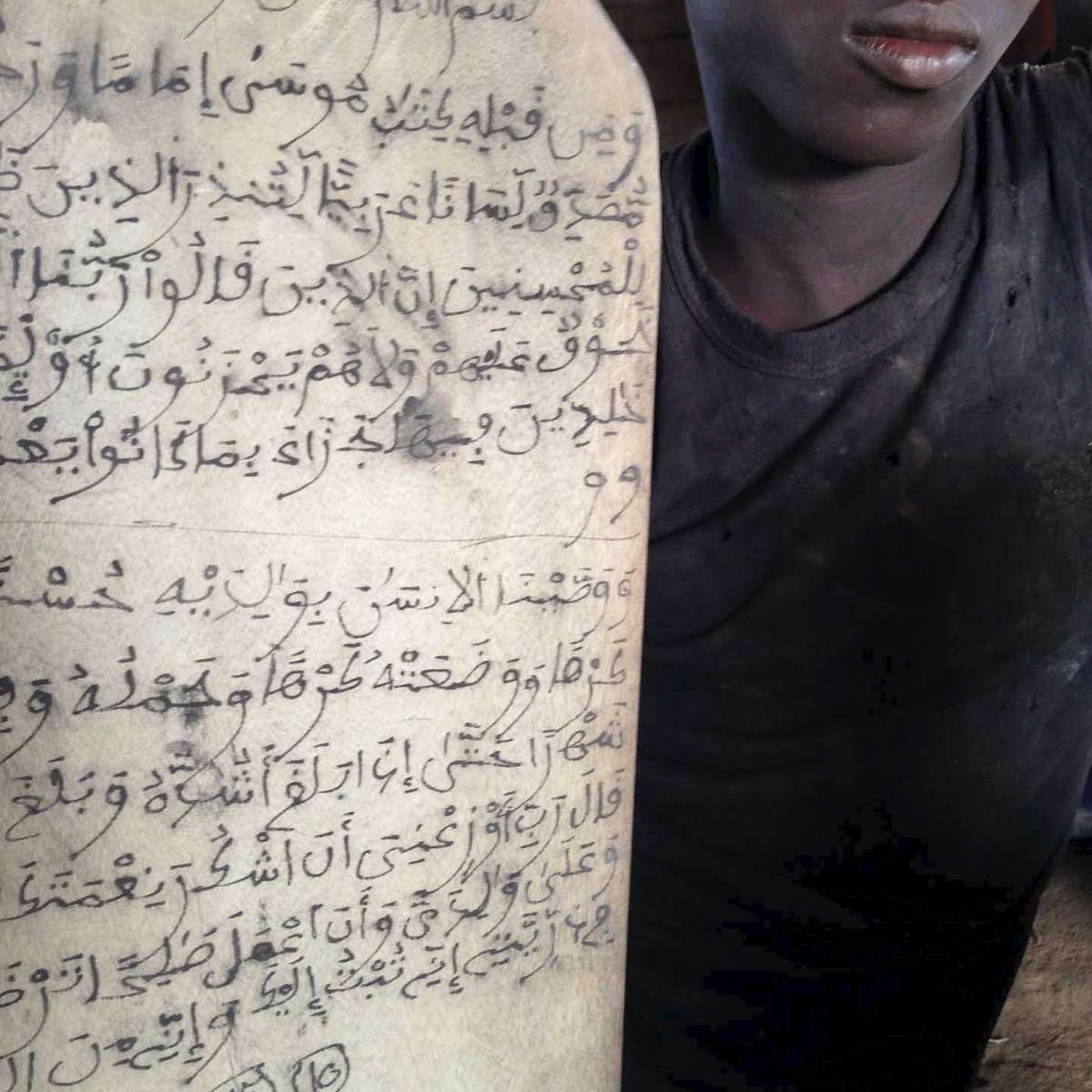 A young boy studying Koran copies verses onto a wooden tablet in a village in southern Senegal near the border with Guinea-Bissau. March 2014.
