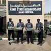 Members of the Hisbah, the Islamic Morality Police, pose for a photo with cans of beer they confiscated and plan to destroy. March 2014.