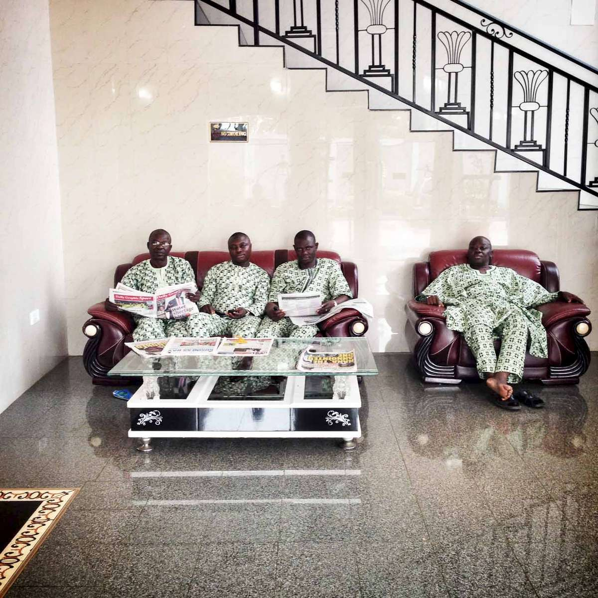 Men wearing matching up and down suits rest in the lobby of a hotel in Accra, Ghana. May 2014.