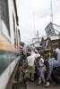 A woman climbs onto the train as other passengers push and shove to get on too at the Abeko stop just outside of the sprawling megacity of Lagos.
