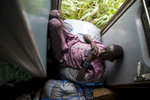 Suleman Abba Akin, the son of the blind in outtake #775 and in rests on the luggage that fills the area between compartments and the doors to the train. Some find this area more comfortable than the overcrowded passenger seats.