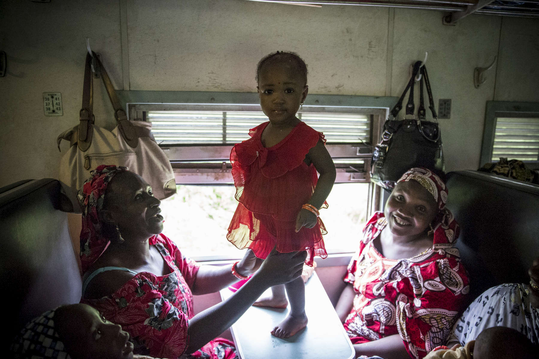 Aisha Lawan, the little girl in the red dress, takes the train from Lagos to Ibadan with her family.