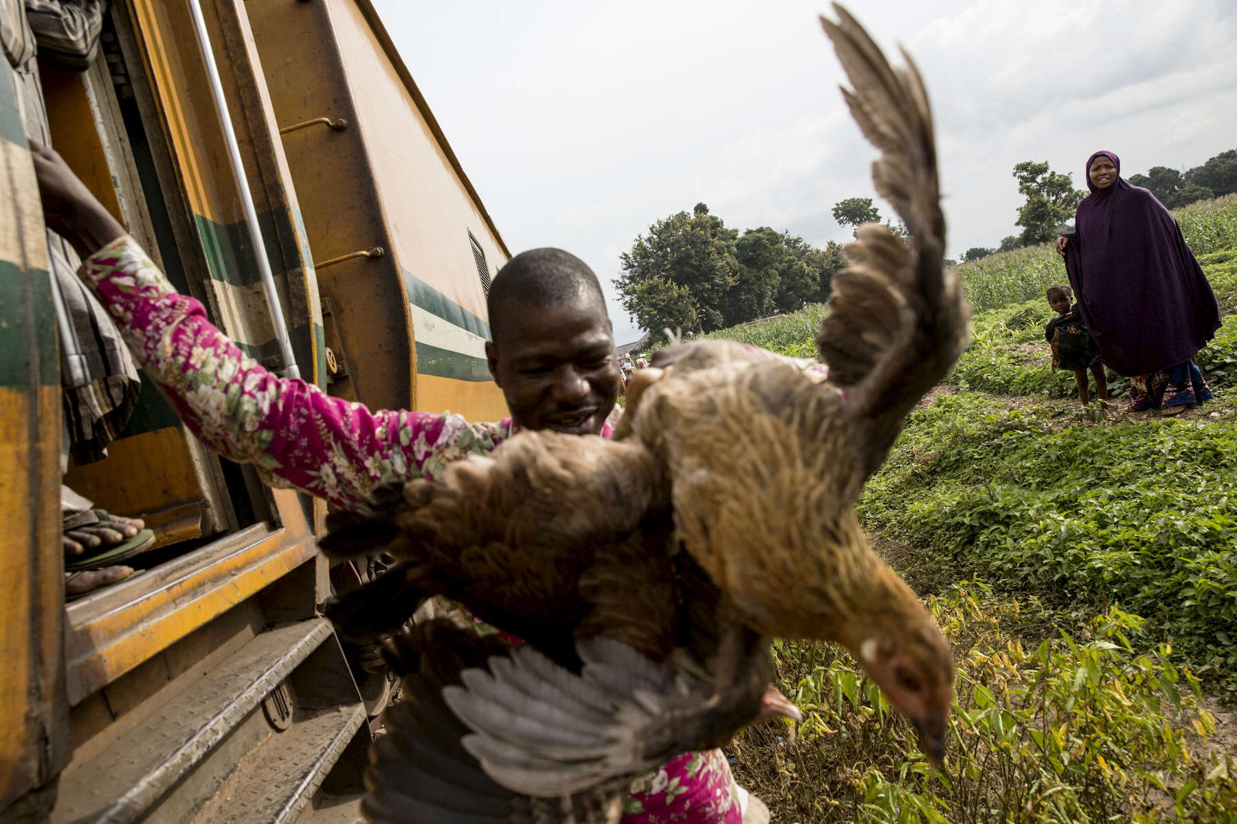 A man gets off the train with two chickens that he purchased a few hours earlier at the Guni stop in Niger State.