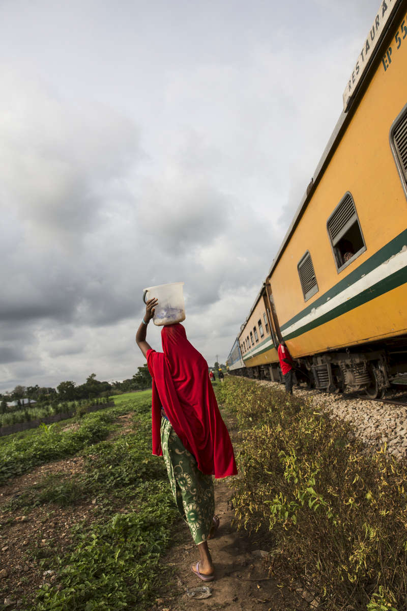 A woman walks by the train at the Guni stop in Munya, Niger State.