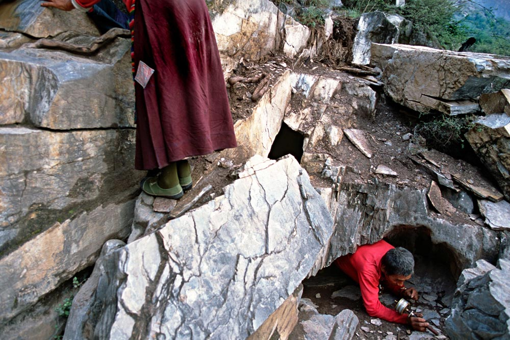 Tibetan pilgrims enter and exit a 'Bardo' hole whilst on a pilgrimage of the Kawa Karpo mountain range. It is believed that such an act is a practice for the next life.Yunnan Province, China