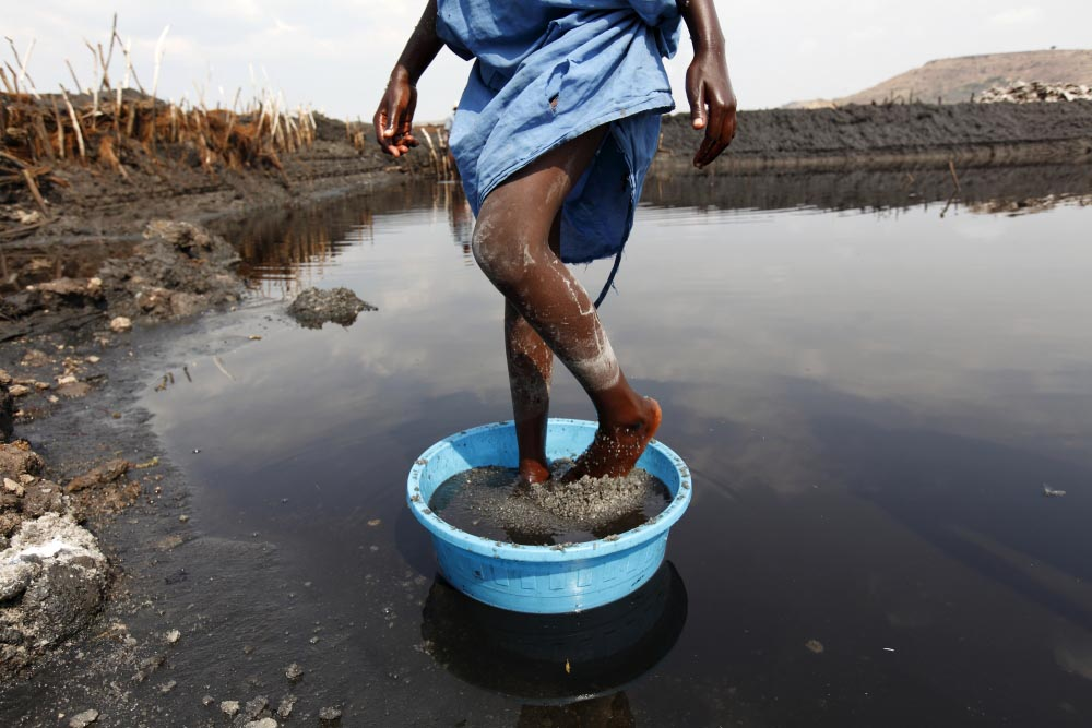 A girl grinds salt with her feet at Lake Katwe in Western Uganda.