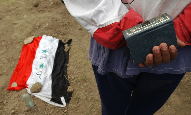 A man holds the Koran next to a grave with an Iraqi flag draped over it at Saddam Children's Park Nurse Villa Hospital in Baghdad. (Chris Schneider/EW Scripps