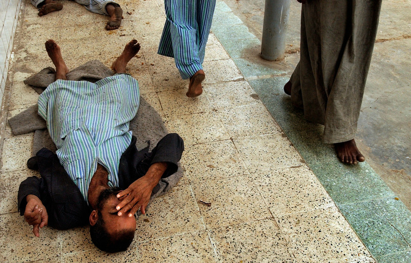 A patient lies on the floor at Rashad psychiatric hospital as other patients file past. Many of the men are extremely mentally ill and a in nearly catatonic state.