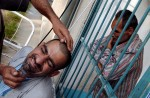 A patient receives a shave from a hospital staff member while another patient waits behind the bars. The hospital was run by the government but is now run by a Shiite charitable organization. The provide care with few resources under desperate conditions after the fall of Saddam's government.