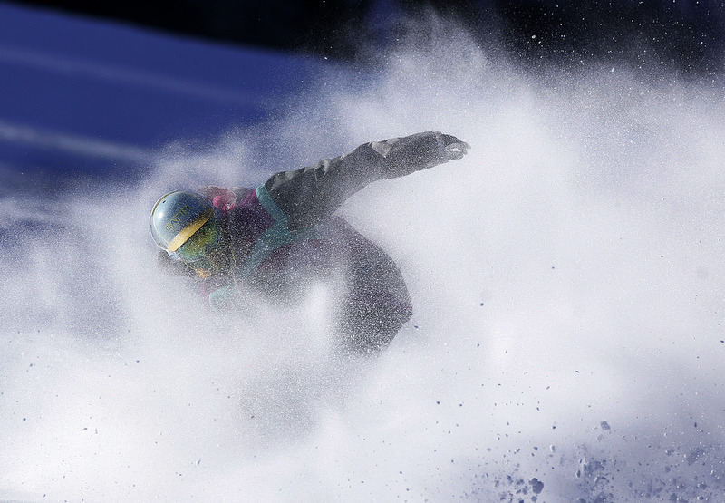 Pat Milbery kicks up a cloud of snow at the bottom of the mountain on opening day at Winter Park Resort in Winter Park, Colorado. Photo by Chris Schneider