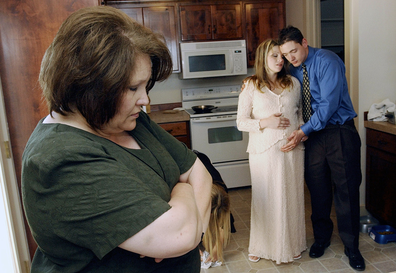 Amber's mother Janice Van Tassell, left, Amber and Jonathan bow their heads in prayer before dinner is served at their wedding. Amber's family has been concerned about their daughter's relationship with Jonathan.