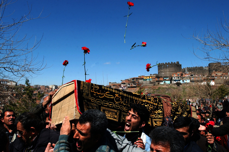 Mourners toss flowers onto the casket of Burhan Karadeniz as it is carried into a cemetery in Diyarbakir, Turkey. Karadeniz was a Kurdish journalist who died in exile and was brought home to be buried. His funeral was a flashpoint of Kurdish and Turkish tensions and was closely monitored by the Turkish police. (Photo by Chris Schneider)