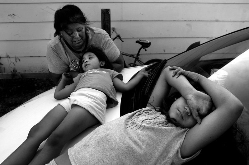 Rachel Ramos, left, talks with her granddaughter Destiny Vargas, 5, center, while her other grandaughter Brooklyn Vargas, 9, right, lays on the hood of their car while taking a break from cleaning their yard of tornado debris in Holly, Colorado. Ramos' house was destroyed by the tornado but they are rebuilding their home. (Photo by Chris Schneider)