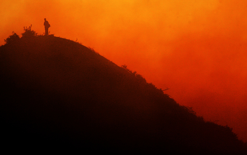 A lone firefighter stands on a mountain top at dusk near New Castle, Colo., on Tuesday, June 19, 2007. More people were evacuated Tuesday after the fire flared up in the afternoon. (Photo by Chris Schneider)