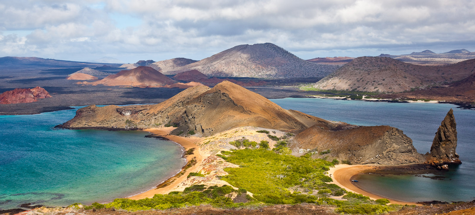 The view of Bartolomé Island with Pinnacle Rock on the right. Bartolomé Island (Spanish: Isla Bartolomé) is a volcanic islet in the Galápagos Islands group. It is a volcanic islet just off the east coast of Santiago Island. It is one of the {quote}younger{quote} islands in the Galápagos archipelago. This island, and Sulivan Bay on Santiago island, are named after naturalist and life-long friend of Charles Darwin, Sir Bartholomew James Sulivan, who was a Lieutenant aboard HMS Beagle. Photo by Jay Graham