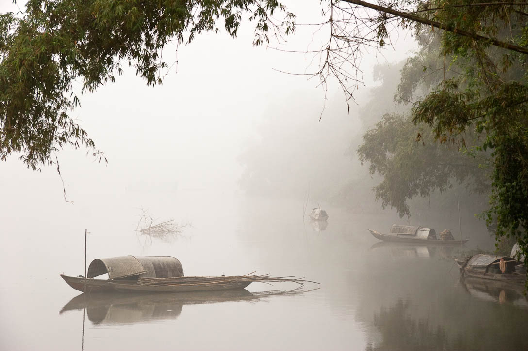 Boats in the early morning mist on a river between Hoi An and My Son, Vietnam. This photo won honorable mention in the International Photography Awards (IPA) 2009. Photo by Jay Graham
